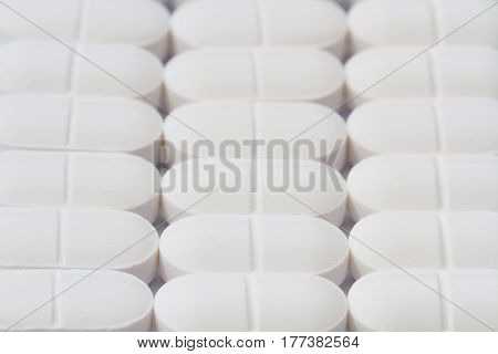 Rows and lines of white tablets, pills, drugs and medicines for pain relief such as headaches in a medical background image representing drug production or manufacturing.