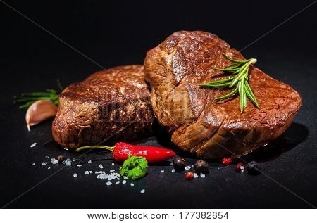 grilled beef fillet steaks with spices on dark background