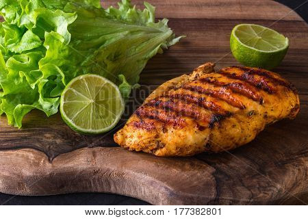 Grilled chicken breast served with green fresh salad lime and chili sause on wooden cutting board