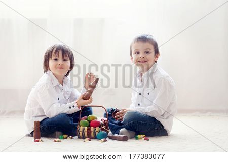 Two Adorable Little Children, Boy Brothers, Having Fun Eating Chocolate Bunnies