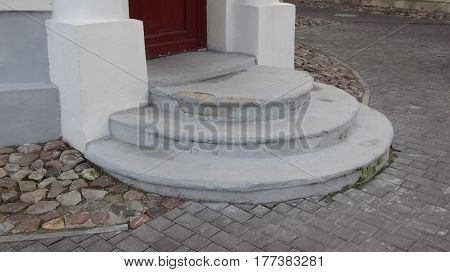 Semicircular steps to the old red door to the pharmacy, on the street