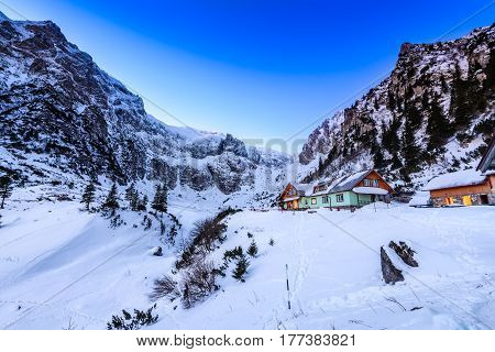 Carpathian Mountains Romania. Winter twilight in Bucegi Mountains Natural Park Malaiesti valley and touristic chalet.