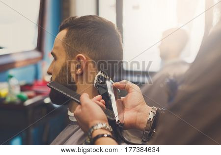 Barber make haircut with hair clipper in barbershop, closeup of client's head. Stylish hairdresser in male hair salon