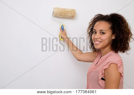 Woman Painting The Wall Of Her House