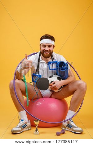 Portrait of a happy sports man sitting on a fitness ball and showing thumbs up gesture isolated on a orange background