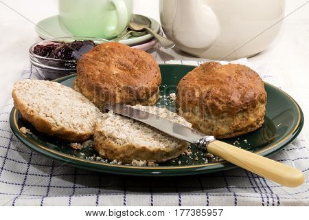british wheaten scone with butter and knife on a green plate