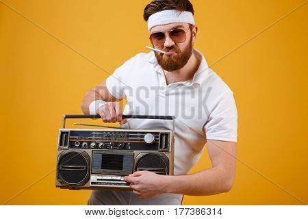 Picture of handsome young man wearing sunglasses holding tape recorder and cigarette dressed in white t-shirt isolated over yellow background. Looking at camera.