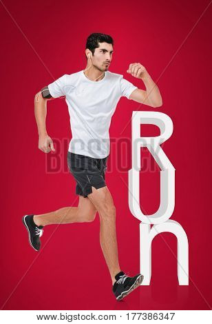 Side view full length portrait of a concentrated young sports man running with earphones isolated on a red background