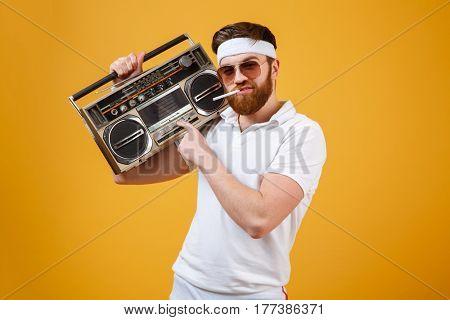 Photo of handsome young man wearing sunglasses holding tape recorder and cigarette dressed in white t-shirt isolated over yellow background. Looking at camera.