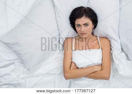 Young woman lying on bed awake unsatisfied