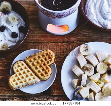 Two wafer cakes in the shape of heart lie on a small plate on a served wooden table. Next to a plate of sliced bananas, a bowl of cottage cheese and a fondue with chocolate