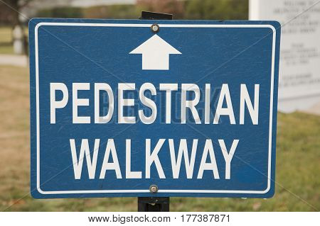 A blue pedestrian walkway sign with white text and arrow