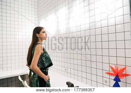 Pretty young woman stading and looking at glowing inscription on the wall in cafe