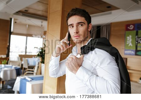Side view of Cool man in shirt which standing in restaurant and talking on phone