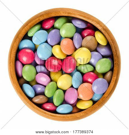Colorful chocolate candies in wooden bowl. Sugar-coated chocolate confectionery in eight different colors. Oblate spheroid shaped candies. Macro food photo close up from above on white background.