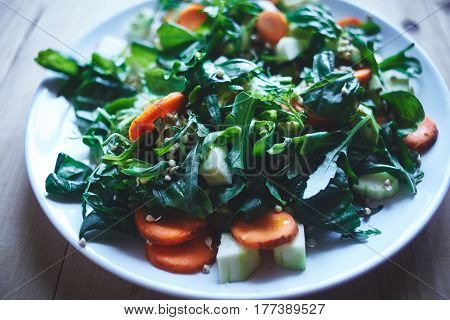 Fresh salad of vegetables and greens on a plate on a wooden background. Salad consists of carrots, Sprouted buckwheat grains, zucchini, lettuce, spinach, Arugula and basil leaves. To the salad served whole-grain bread.