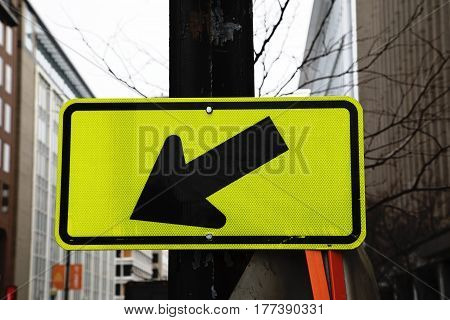 A fluorescent yellow road sign with black arrow