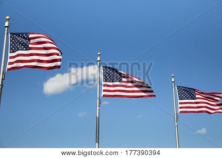 Three American flags blowing in the wind