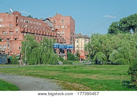 Dnipro Ukraine - July 05 2013: Building is made of red bricks surrounded by a green lawn and trees in the middle of summer