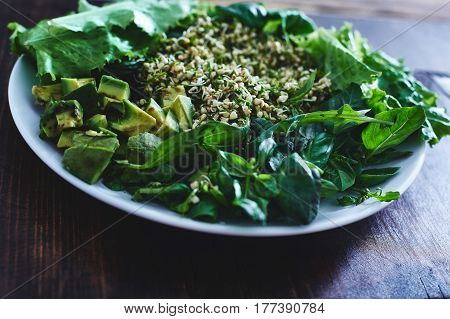Fresh salad of vegetables and greens on a plate on a wooden background. Salad consists of Sprouted buckwheat grains, Finely chopped dill, zucchini, avocado, lettuce, spinach, Arugula and basil leaves. To the salad served whole-grain bread.