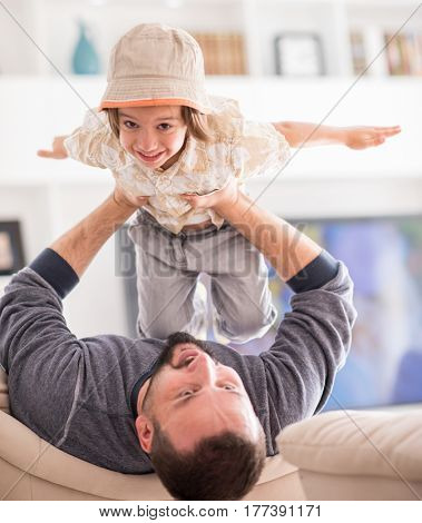 Flying child in father hands on sofa