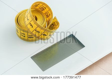 Curved measuring tape. Measuring tape of the tailor. Closeup view of yellow measuring tape on weighing-machine