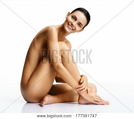 Smiling naked woman with perfect body on white background. Beautiful female sitting on the floor touch leg. Beauty & Skin care concept
