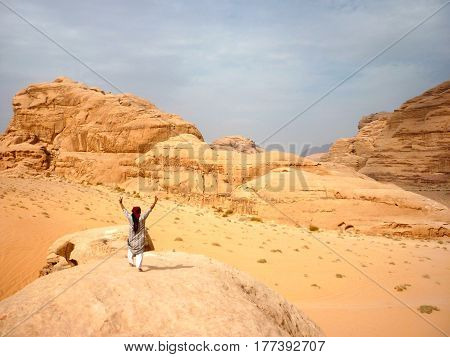 Bedouin standing on a rock in Wadi Rum desert in Jordan