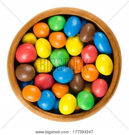 Colorful chocolate peanut candies in wooden bowl over white. Peanuts coated in milk chocolate with candy shell in different colors. Isolated macro food photo close up from above on white background.
