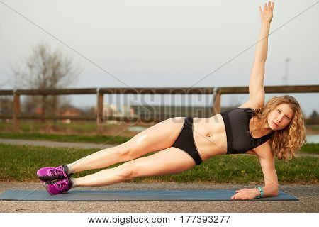Portrait of a fitness woman sitting training outdoor