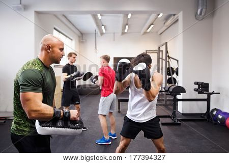 Handsome fit hispanic man boxing with his personal trainer. Athlete boxers wearing boxing gloves sparred in boxing gym.