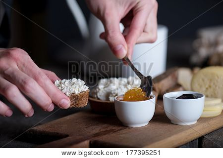 Man's hand holding spoon and putting jam on bread with fresh homemade ricotta cheese