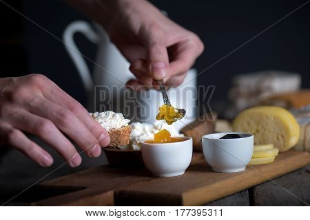Man's hand holding spoon and putting jam from white bowl on bread with fresh homemade ricotta cheese, selective focus