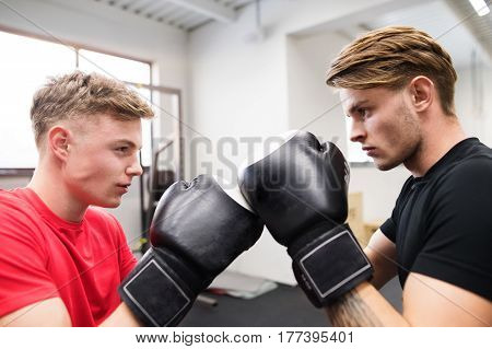 Two fit handsome men boxing. Two athlete boxers wearing boxing gloves sparred in boxing gym.