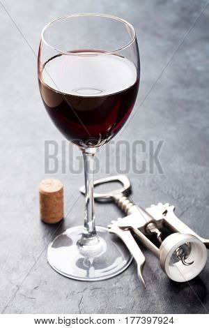 Red wine glass and corkscrew on stone background