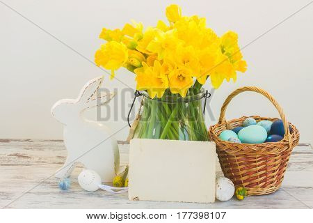 Easter eggs hunt - white rabbit, basket with painted blue eggs and daffodils bouquet, copy space on white paper note