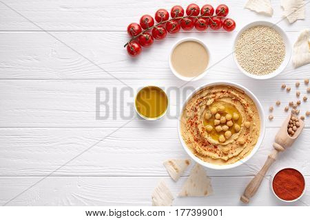 Hummus homemade arabic healthy vegan dip chickpeas paste snack flat lay with ingridients, tahini, paprika, olive oil, cherrys, pitta bread on white table. Healthy vegetarian nutrition food