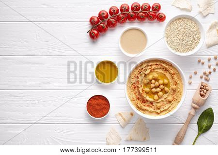 Hummus traditional Israel healthy vegan dip chickpeas paste snack flat lay with natural ingridients, tahini, paprika, olive oil, pitta on white table. Healthy vegetarian diet nutrition protein food