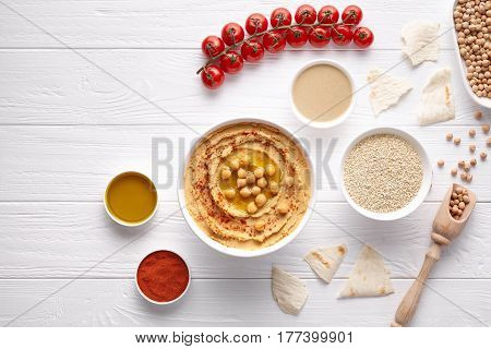 Hummus traditional Mediterranean healthy vegan dip chickpeas paste snack flat lay with natural ingridients, tahini, paprika, olive oil, pitta on table. Healthy vegetarian diet nutrition protein food