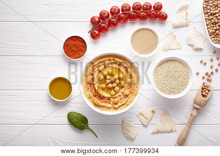 Bowl of hummus mediterranean healthy vegan dip chickpeas paste snack flat lay with natural ingridients, tahini, paprika, olive oil, pitta on table. Healthy vegetarian diet nutrition protein food