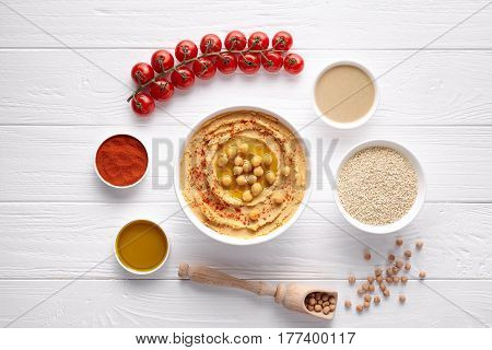 Traditional hummus Israel healthy vegan dip chickpeas paste snack flat lay with natural ingridients, tahini, paprika, olive oil, pitta on table. Healthy vegetarian diet nutrition protein food