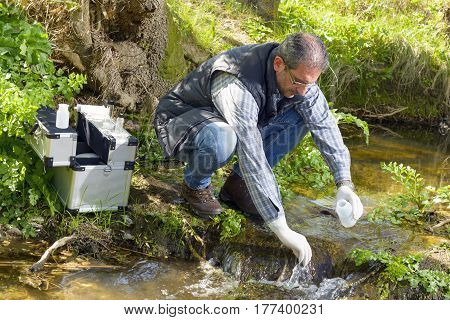 Scientist and biologist hydro-biologist takes water samples for analysis.