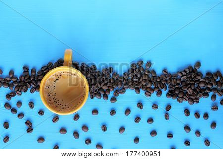 flat layout with a yellow mug of frothy espresso on a blue table with roasted grains / invigorating aroma of the coffee