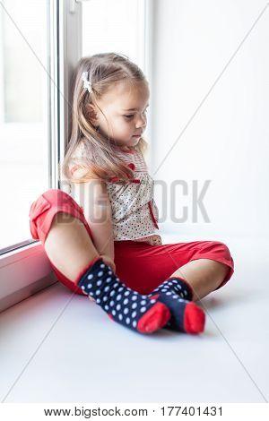 Upset little child girl sitting near the window