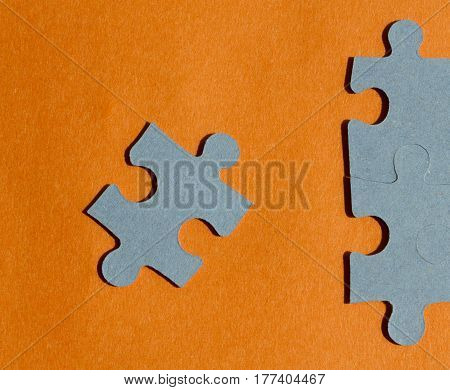 Jigsaw puzzle pieces on orange background macro view