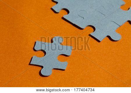Jigsaw puzzle pieces on bright orange background horizontal