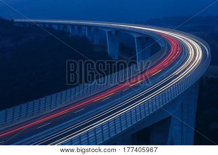 Blurred lights of vehicles driving on a tall viaduct with wind barriers long exposure. Rush hour on the road connectivity and internet concept background with copy space.