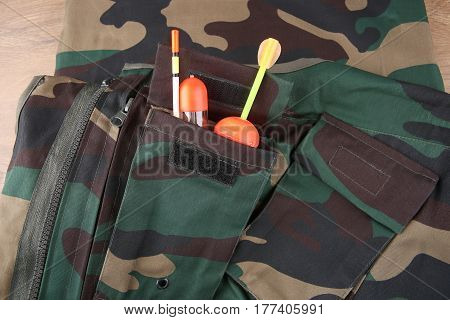 Fabric camouflage pattern with pockets and fishing accessories. Fragment of vest. Abstract camouflage textile background.