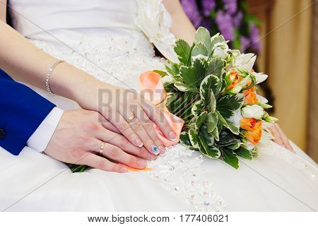 Bride's hand lies on a hand of the groom and stroked a golden ring on the background of a bouquet of flowers
