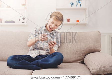 Gaming online games app concept - teenage boy playing with mobile and headphones, enjoying sitting on sofa in living room at home